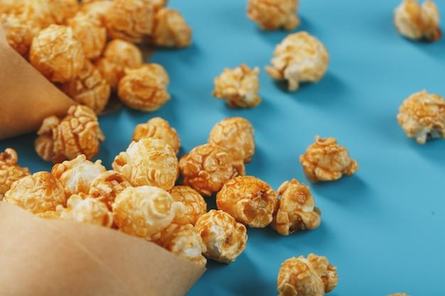 Palomitas de maíz en glaseado de caramelo en un sobre de papel sobre un fondo azul.