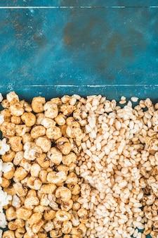 Palomitas de maíz y granos de trigo sobre un fondo azul.