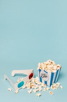 Las palomitas de maíz llenaron la caja con gafas 3d contra el fondo azul