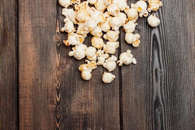 Palomitas de maíz en una mesa de madera, entretenimiento de bocadillos mientras ve una película