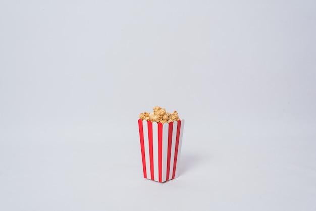Palomitas de maíz de película en fondo aislado cubo rayado
