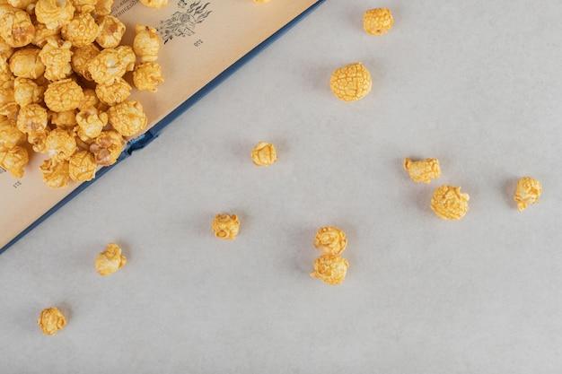Palomitas de maíz recubiertas de caramelo esparcidas por encima y delante de un libro abierto sobre fondo de mármol.
