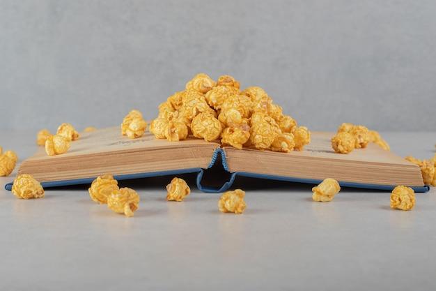 Palomitas de maíz con sabor esparcidas por encima y delante de un libro abierto sobre una mesa de mármol.
