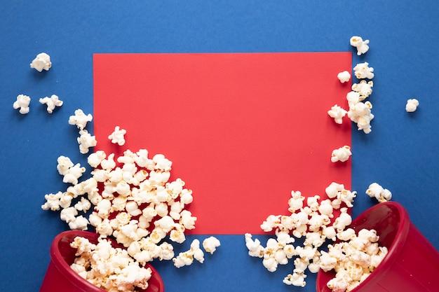 Palomitas de maíz sobre fondo azul y tarjeta roja vacía