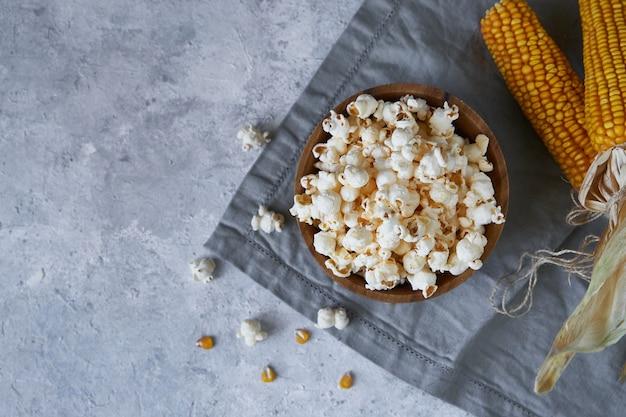 Palomitas de maíz tradicional en un tazón de madera y mazorcas de maíz sobre la mesa.