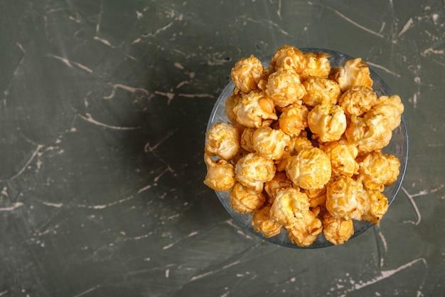Palomitas de maíz en vaso de papel sobre superficie verde