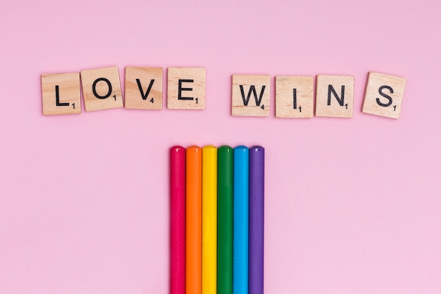 Palos de colores del arco iris y signo de amor gana
