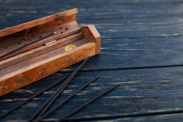 Palos de sándalo en una mesa de madera negra.