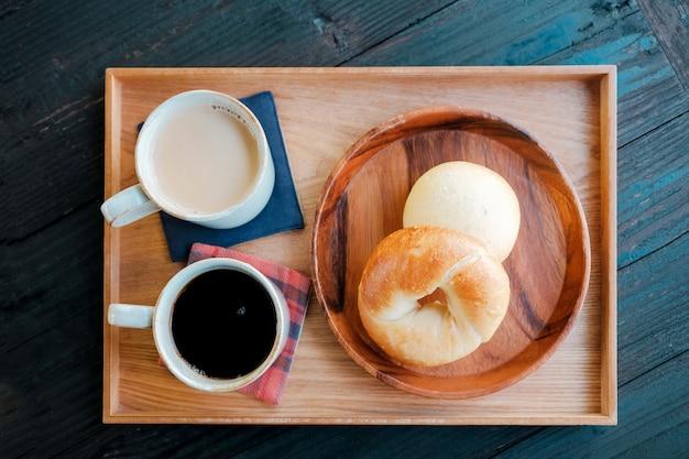 Pan de bagel casero fresco y café caliente, té con leche en bandeja de madera por la mañana
