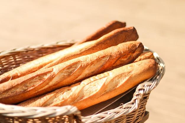 Pan baguette francés en una panadería de pie en una cesta de mimbre en el mostrador