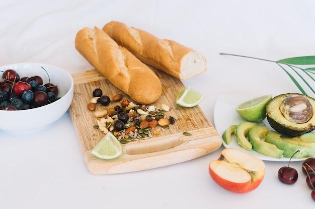 Pan de baguette frutas secas y frutas sobre fondo blanco