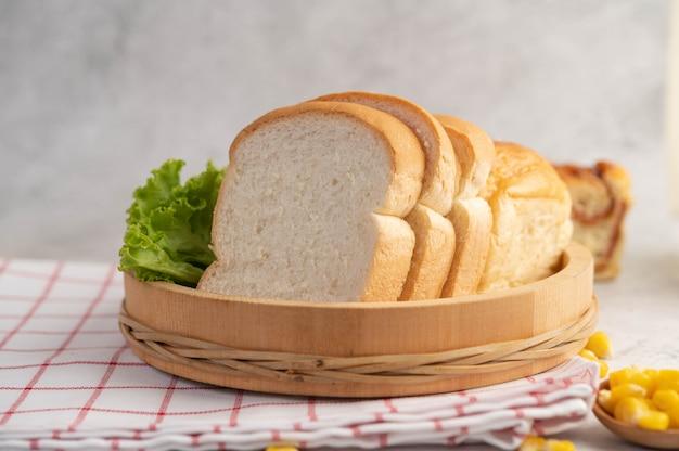 Pan en una bandeja de madera sobre un paño rojo y blanco.