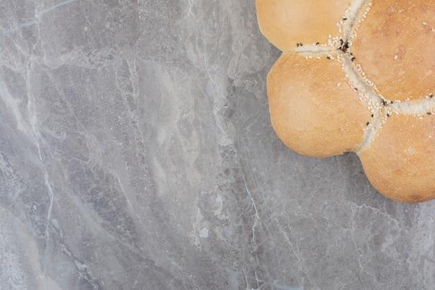 Un pan blanco redondo sobre superficie de mármol.