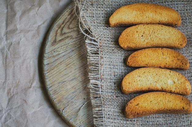 Pan blanco tostado sobre lienzo y papel de envolver vintage, tonificado y descolorido