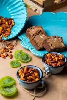Pan de cacao y nueces en un plato turquesa servido con kiwi seco y nueces