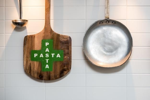 Pan, cáscara de madera y una cuchara de metal colgando de una pared blanca