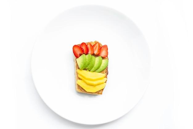 Pan casero cubierto con mantequilla de maní, cubra con fresas, mango y aguacate en un plato blanco. alimentos saludables para adelgazar. concepto de desayuno saludable.