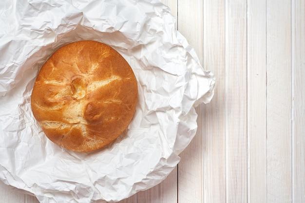 Pan casero fresco en el libro blanco y el fondo de madera blanco.