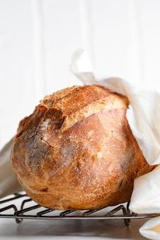 Pan casero recién horneado sobre una tabla de madera y una mesa de mármol gris claro decorado con una toalla textil.