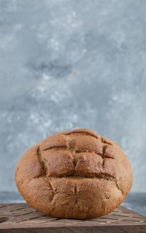 Pan de centeno recién cocido sobre tabla de madera. foto de alta calidad