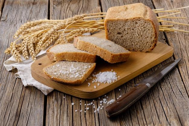 Pan de centeno en rodajas recién horneado sobre tabla para cortar madera