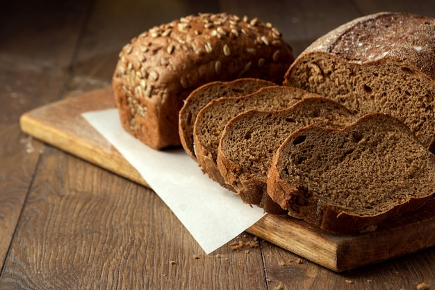 Pan de centeno en rodajas recién horneado sobre una tabla para cortar madera