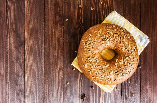 Pan de centeno con semillas de girasol en una toalla en el tablero de madera