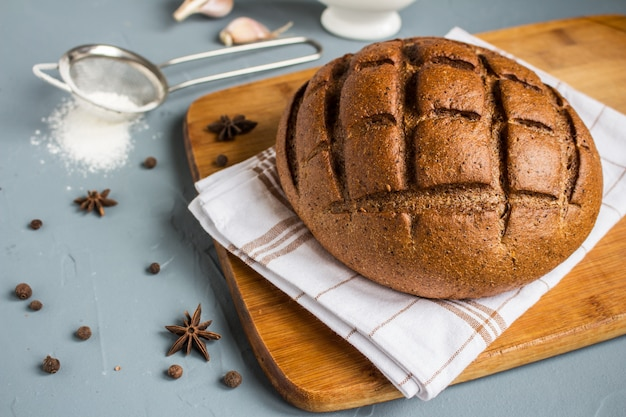 Pan de centeno en la toalla en la mesa con especias
