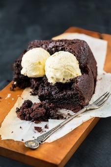 Pan de chocolate vegano saludable (pastel) con cucharadas de helado de vainilla sobre fondo gris oscuro