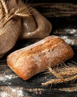 Pan ciabatt con harina y trigo en la mesa