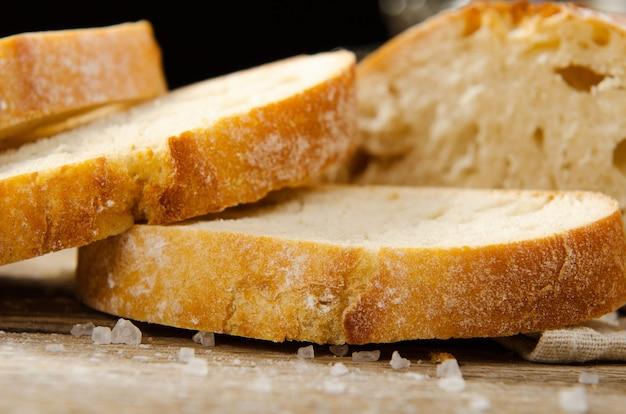 Pan de ciabatta. rebanadas de ciabatta con el ajo, sal en la tabla de madera en el paño de lino.