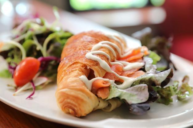 Pan croissant con salmón y ensalada sobre fondo de madera