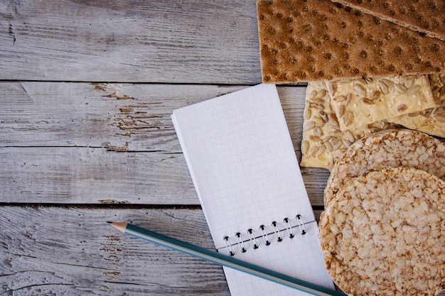 Pan crujiente, copos, trigo sarraceno, galletas con girasol sobre un fondo texturizado