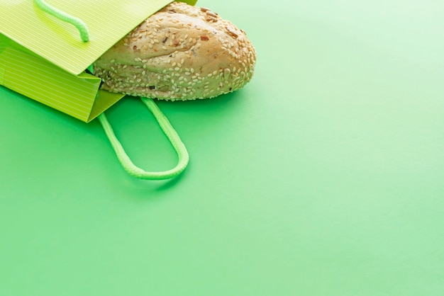 Pan crujiente fresco en el bolso de compras en un fondo verde.