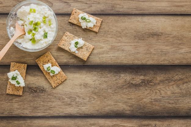 Pan crujiente con queso crema fresco sobre fondo de madera