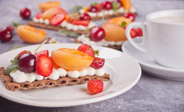 Pan crujiente con queso crema, frutas y bayas