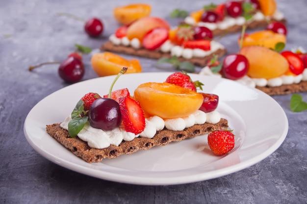 Pan crujiente con queso crema, frutas y bayas.