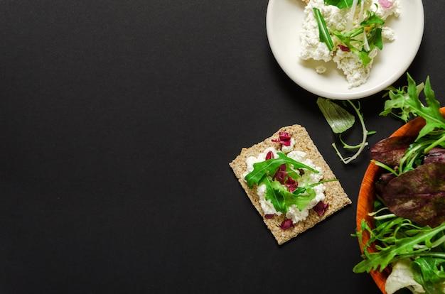 Pan crujiente, queso crema en un plato, mezcla de verduras frescas sobre un fondo negro.