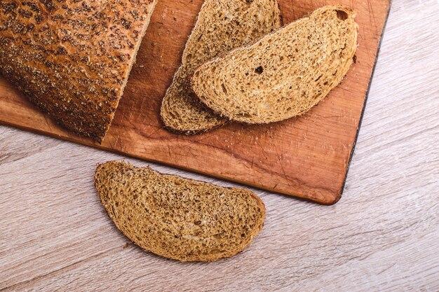 Pan crujiente sobre una tabla de madera. pan de salvado gris en rodajas sobre una tabla de madera.