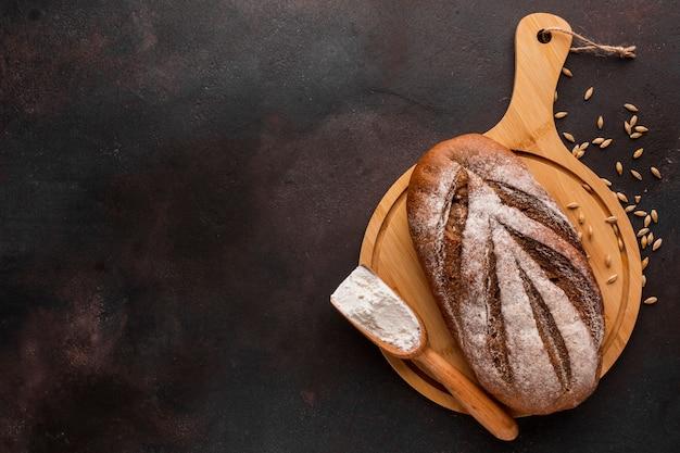 Pan crujiente sobre tabla de madera con semillas de trigo