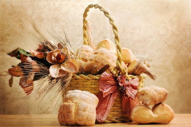 Pan dentro de la cesta con flores de magnolia y trigo
