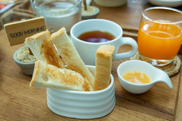 Pan para el desayuno con té y jugo de naranja.