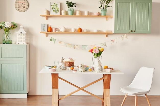 Pan dulce de pascua, pastel de pascua y huevos multicolores con tulipanes y un conejo blanco. concepto de desayuno de vacaciones con espacio de copia.
