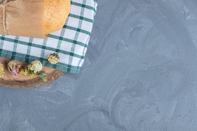 Pan envuelto en papel sobre un mantel doblado sobre fondo de mármol.