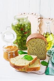 Pan de espinacas recién horneado en una mesa de madera blanca. estilo rústico comida de panadería.
