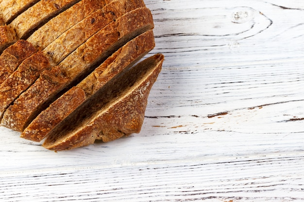 Pan francés rebanado, en una tabla de madera con espacio para texto