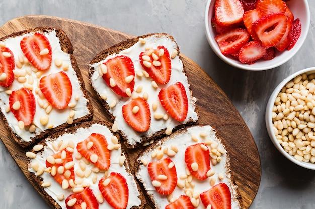 Pan con fresa, piñones y queso crema sobre fondo gris