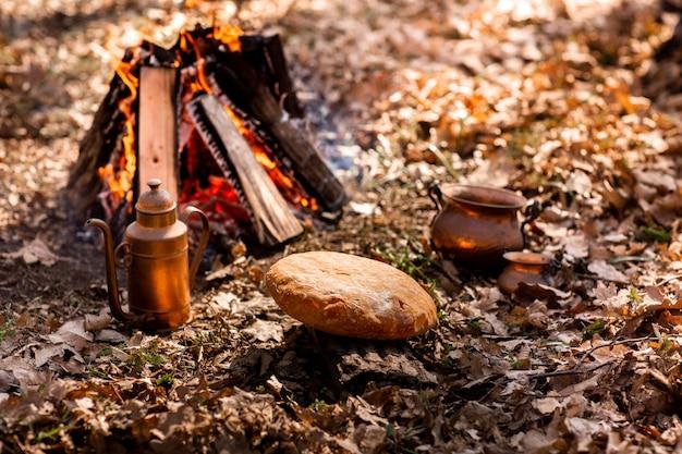 Pan fresco casero y hoguera en el bosque de otoño.