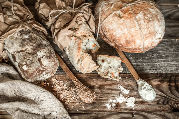 Pan fresco y cuchara de madera sobre fondo de madera vieja