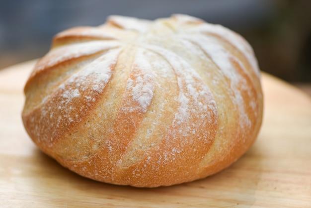 Pan fresco de la panadería en el concepto hecho en casa de madera de la comida del desayuno, barra de pan redonda